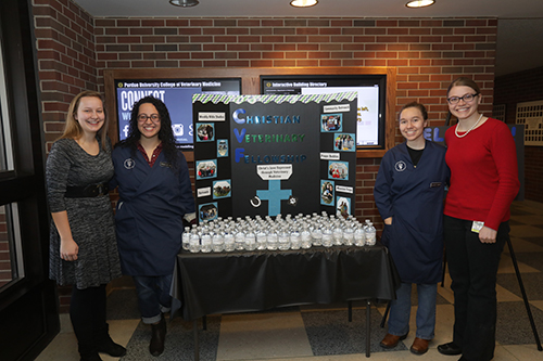 Members of the Christian Veterinary Fellowship student organization host a display table with water for visiting families (left-right): Hannah Clinton, CVF president; Jessica Linder, treasurer; Katelyn Gnegy and Emily Christenson, social and mission chair.