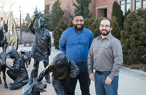 Veterinarian Alejandro Morales (right), assistant director of ARCAS in Peten, Guatemala, braves the Indiana winter for an outdoor photo-op by the Continuum sculpture with Will Smith, II, PVM director of international programs.