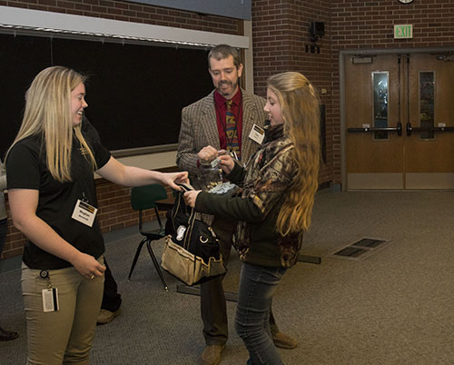 Equine Club President Meghan Wanstrath, of the DVM Class of 2019, awards a give-away to Dakota Szakacs, a horse enthusiast in the 7th grade from St. Joseph County, as Dr. Tim Lescun looks on during the Horseman's Forum in Lynn 1136.